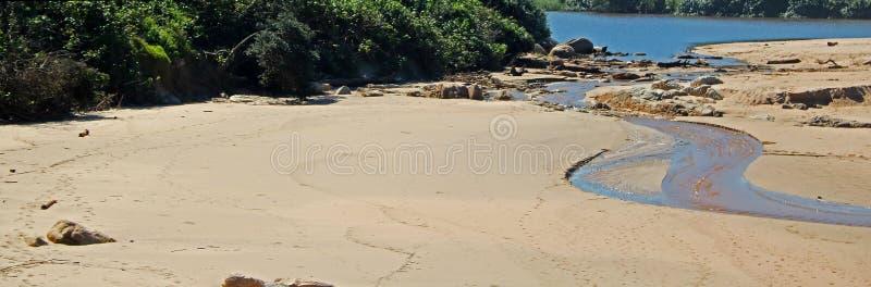 Beach and rivulet running into lagoon at Ramsgate, Kwazulu Natal. royalty free stock images