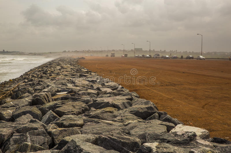 Beach road in Accra, Ghana. Sea shore of Atlantic Ocean in Accra (Ghana, West Africa). Strengthening stones at the coastline. Cars at the beach road stock images