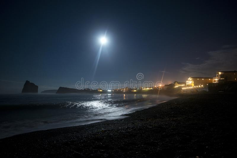 Beach at Rocher Perce, Quebec, Canada. Rocher Perce illuminated at night on beach in Quebec, Canada with full moon stock photo