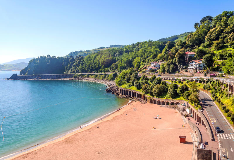 Beach of San Sebastian. In Spain, beside are the mountains on a sunny day. You can see the road with cars royalty free stock photo