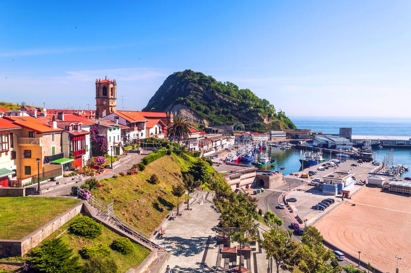 Beach of San Sebastian. In Spain, beside are the mountains on a sunny day. You can see the road with cars and the port with boats royalty free stock photography