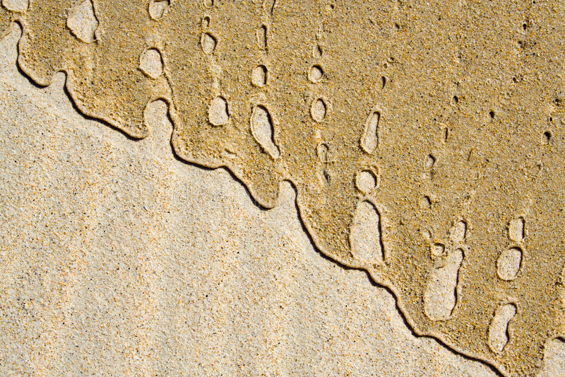 Beach sand. A tight-cropped image of beach sand showing marks made by the waves stock images