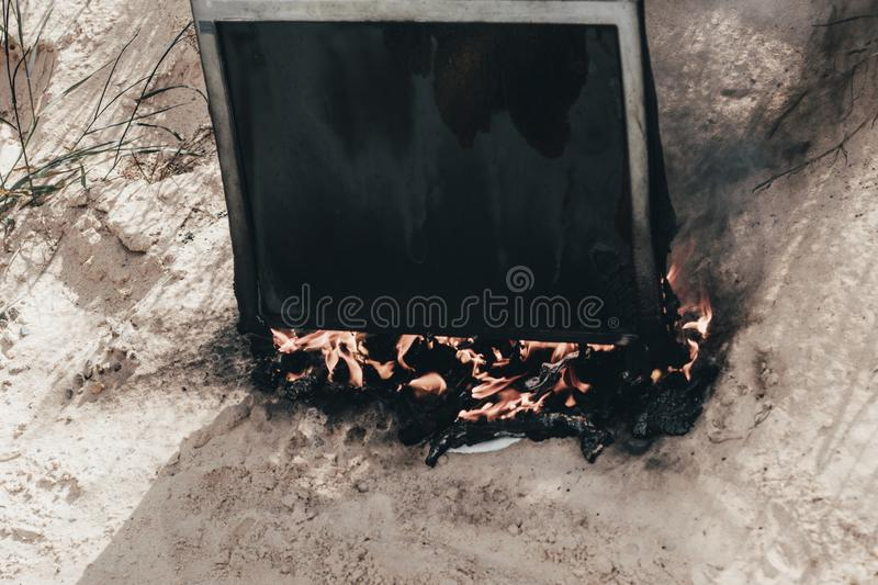 Beach sand. Bright sun. the monitor burns with smoke. Have a keyboard. Flame, firewall, computer, digital, electronic, hot, equipment, heat, screen, black royalty free stock photos