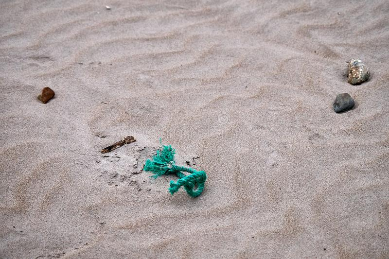 Beach sand, stones and rope. Beach sand, a couple of small stones and green rope stock images