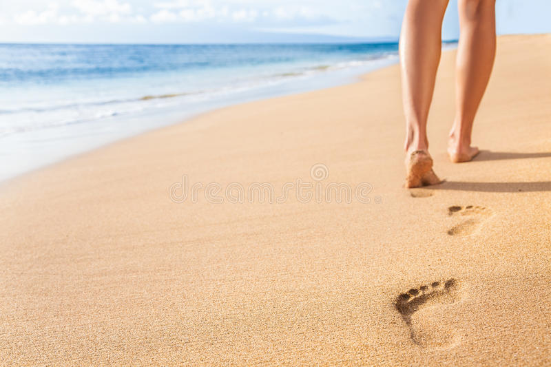Beach sand footprints woman legs walking relaxing. Beach travel - woman relaxing walking on sand beach leaving footprints in the sand. Closeup detail of female royalty free stock photography