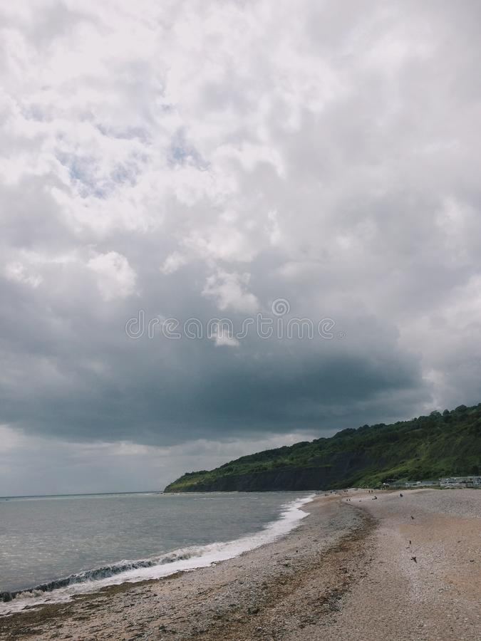 Beach Sand Near Body of Water and Green Mountain Under Cloudy Sky stock photography