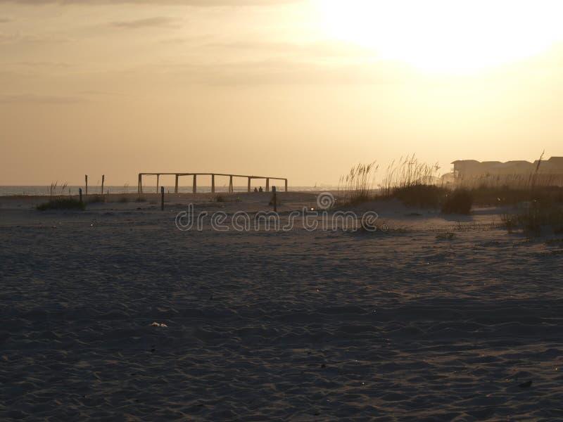 Beach sand ocean waves pier clouds sky royalty free stock image