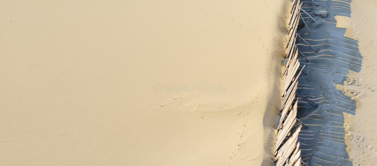 Beach sand protected from wind by wooden wall or barricade line, view from above stock photo
