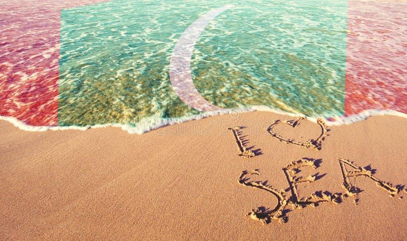 Beach sand, sea and flag Maldives. I love Maldives concept.  royalty free stock photo
