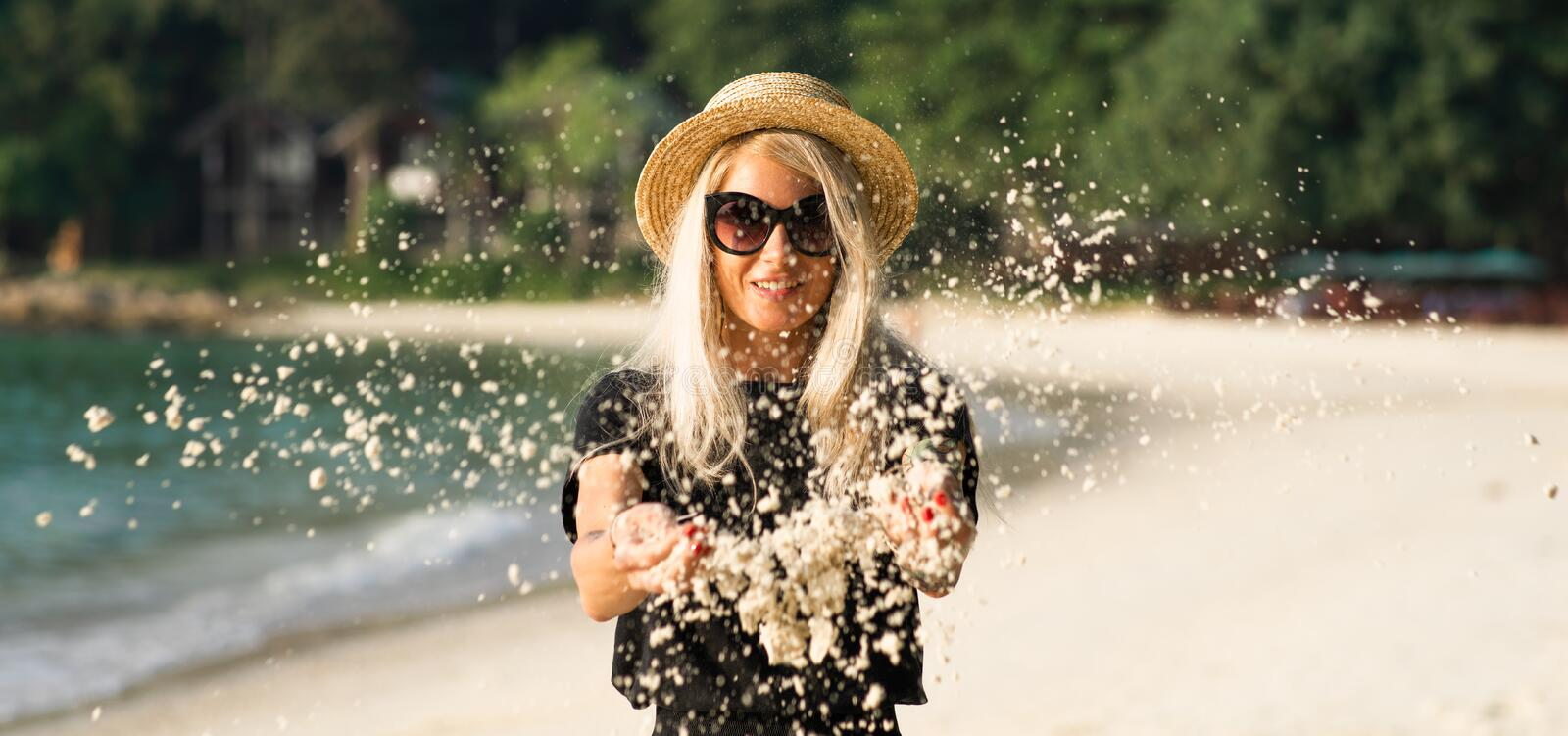 The beach sand wakes up from the hands of a beautiful blonde in sunglasses. Beach vacation. Portrait of a modern girl. stock photos