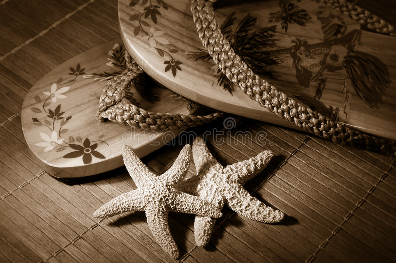 Beach sandals/ sepia tone. Pair of beach sandals with little starfish on floor after a days walk on the beach royalty free stock image