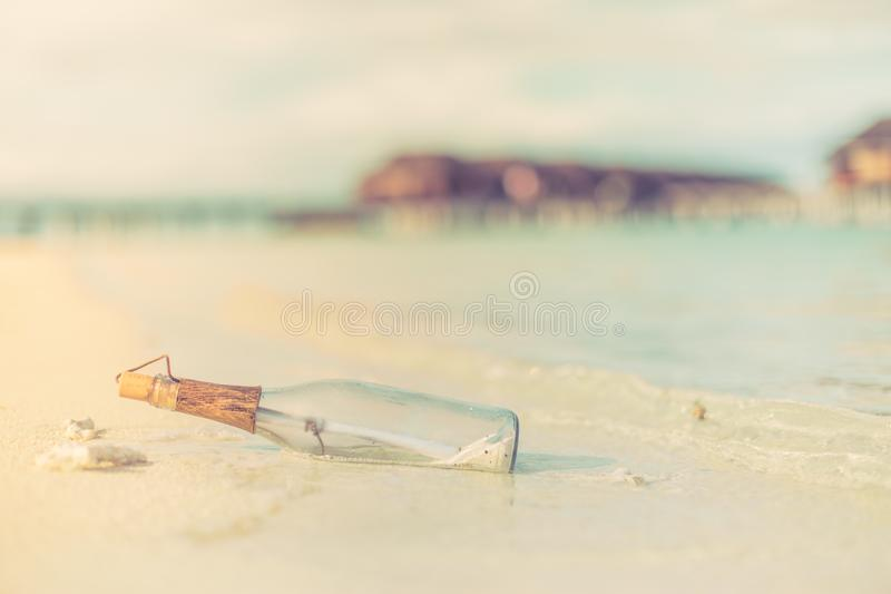 Message in a bottle on a tropical beach and blurred background. Inspire bckground design. Beach scene with message in a bottle stock photography
