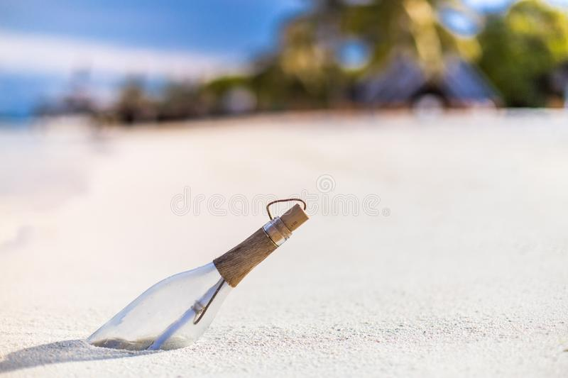 Message in a bottle on a tropical beach and blurred background. Inspire bckground design. Beach scene with message in a bottle royalty free stock photography