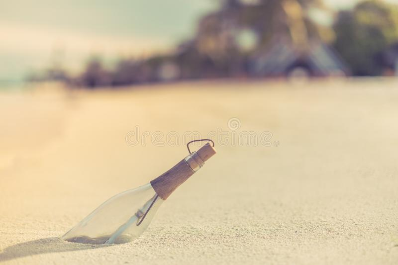 Message in a bottle on a tropical beach and blurred background. Inspire bckground design. Beach scene with message in a bottle stock image