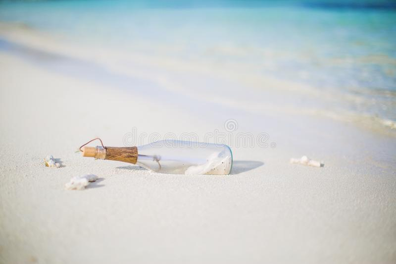 Message in a bottle on a tropical beach and blurred background. Inspire bckground design. Beach scene with message in a bottle stock photo
