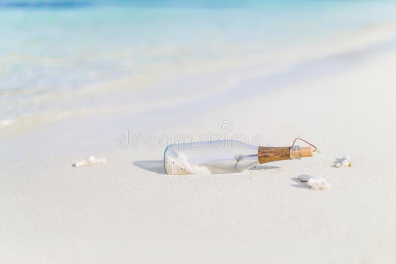Message in a bottle on a tropical beach and blurred background. Inspire bckground design. Beach scene with message in a bottle royalty free stock images