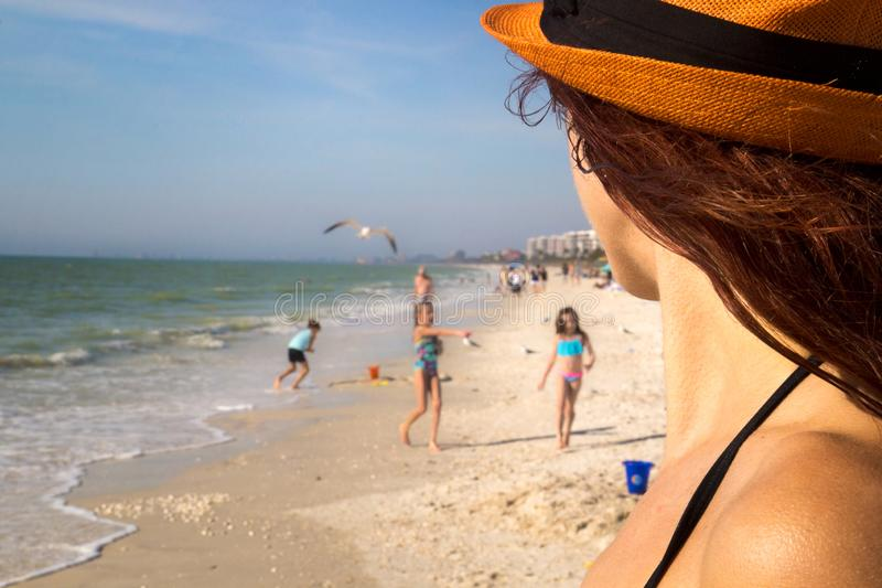 Sandy beach family holiday, pretty woman detail watching children playing on the sun in swimwear at beautiful sea beach in Florida royalty free stock photography