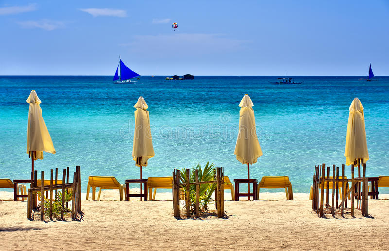 Beach Scene with Sail Boats. And lounging chairs overlooking a clear blue sea stock photos