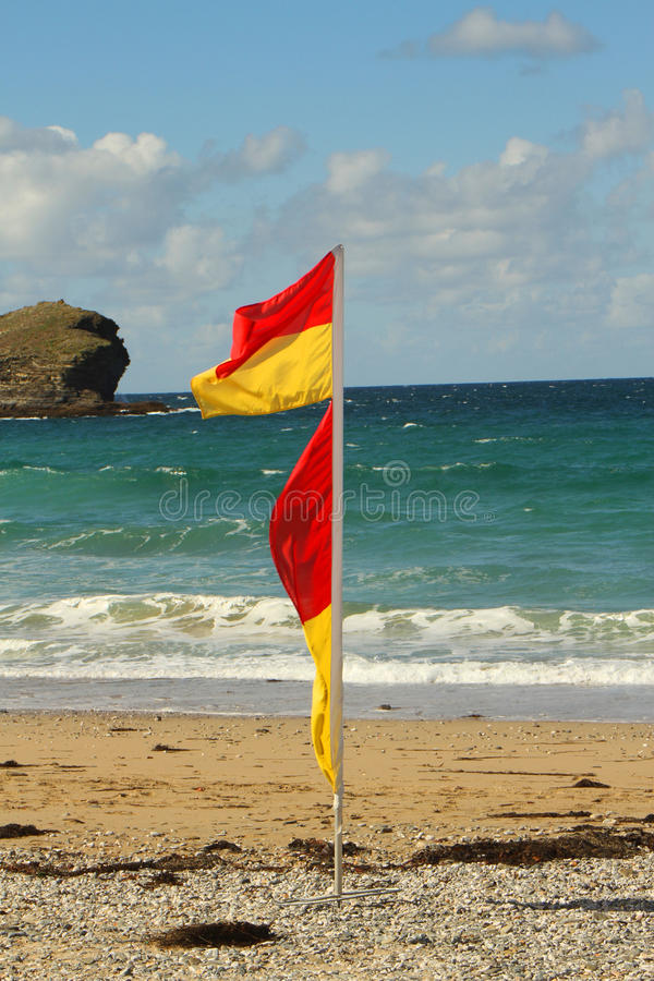 Beach scene. Summer beach scene with safety flag and rock stock photography