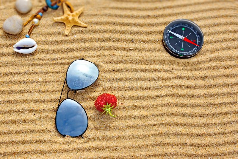 Beach scene with sun glasses, compass starfishs and one strawberry stock photos