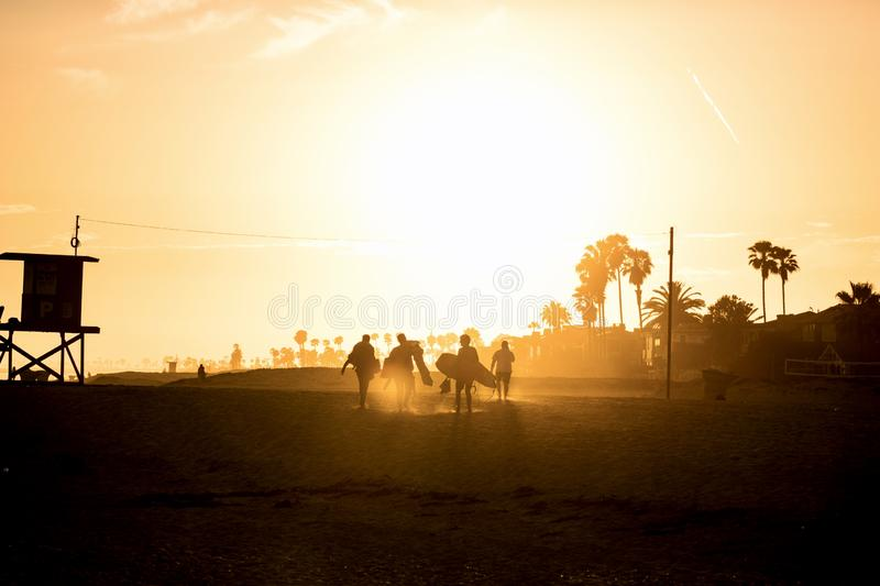 Beach scene in Newport Beach California. Beach scene during sunset.  Silhouettes of a group of body boarders leaving The Wedge beach at the end of a surf session royalty free stock photo