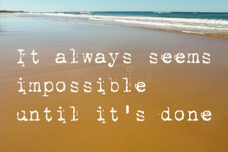 Beach Scene of wet sand with waves in the background and the motivational quote it always seems impossible until it`s done stock images