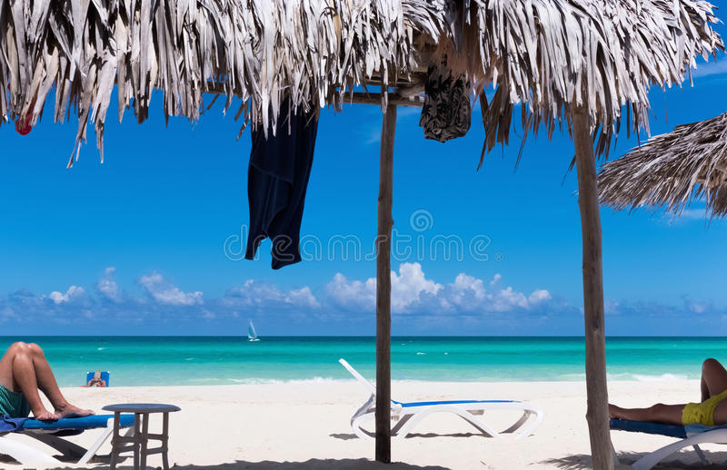 Beach scenery on the dream beach with sun lounger and thatched hut in Cuba - Serie Cuba 2016 Reportage royalty free stock photos