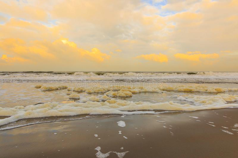 Beach and sea with breakers with thick white and cream-coloured foam stock image