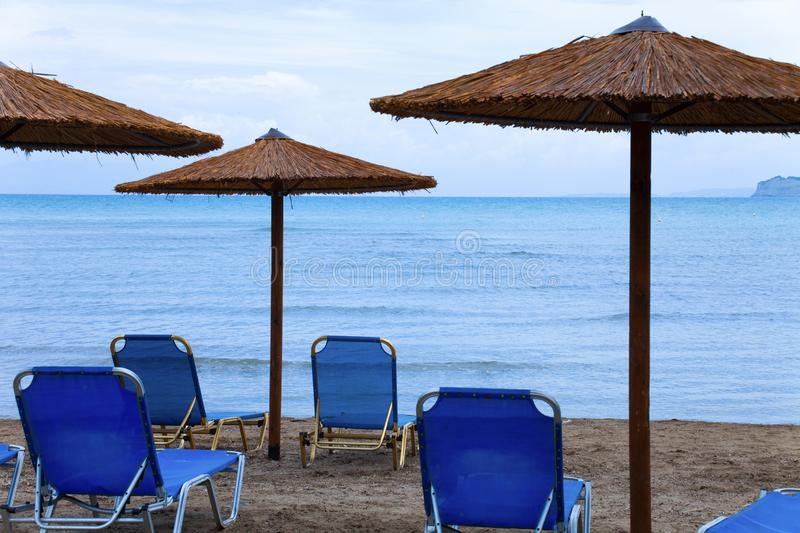 Beach at sea with canyon and sandy beach. Plastic seats on the sandy beach. Holiday concept with beach and sea in the stock image