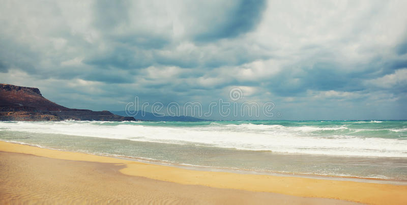 Beach and sea with strong waves, stormy sky, dark clouds background stock image