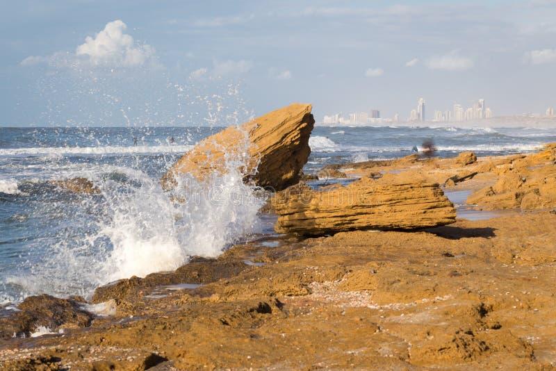 Beach sea wave splash cityscape buildings stone shore. stock images