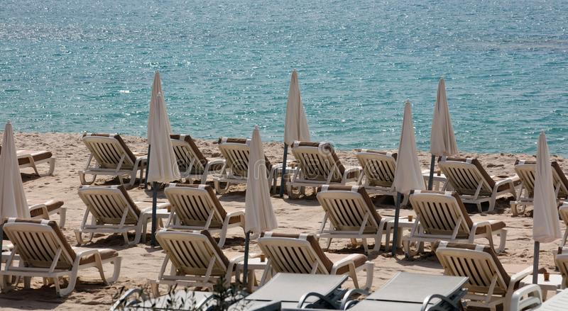 Beach seats and umbrellas at the beach in Cannes south France blue Mediterranean sea. royalty free stock images