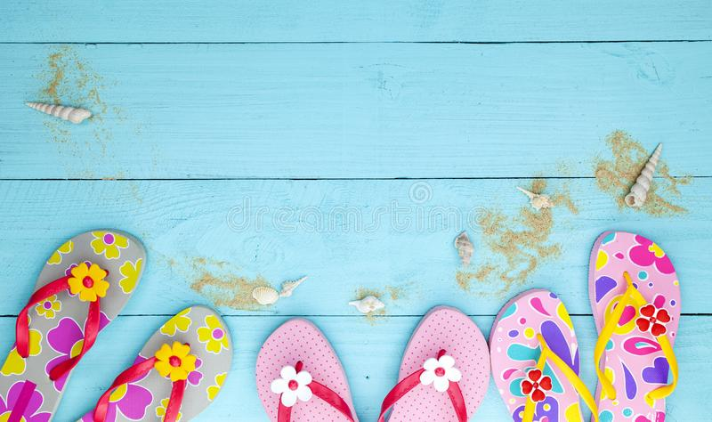Beach shoes with seashell and sand on wood background,Summer holiday concept stock image