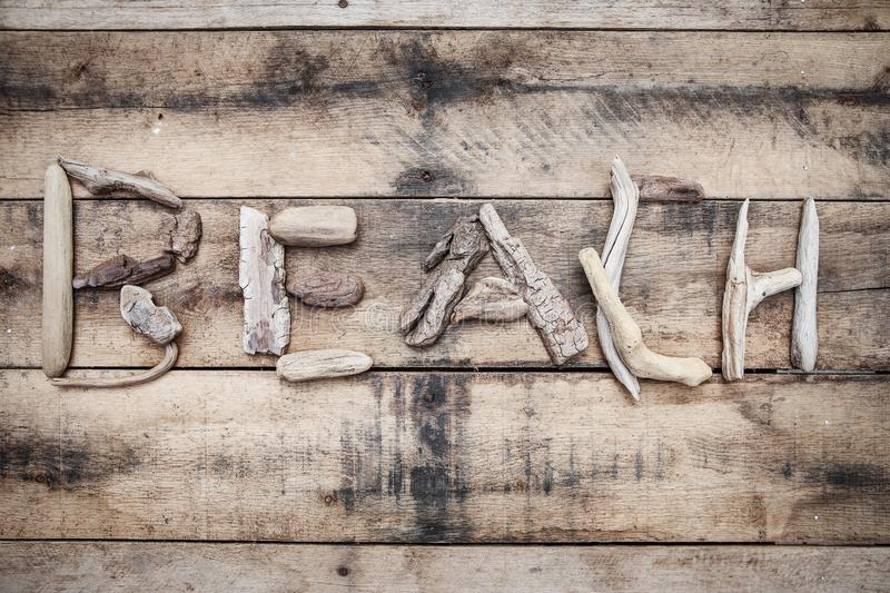 Beach sign made of driftwood on a wooden background royalty free stock photos