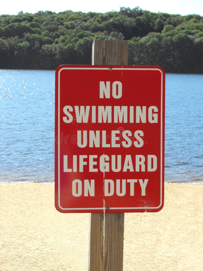 Beach sign warning no swimming unless lifeguard on duty stock images