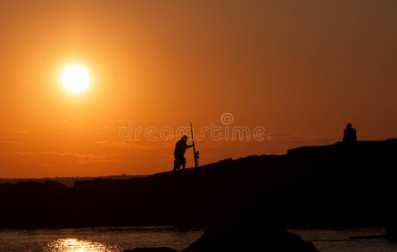 Beach Silhouette of Fisherman Heading Home stock images