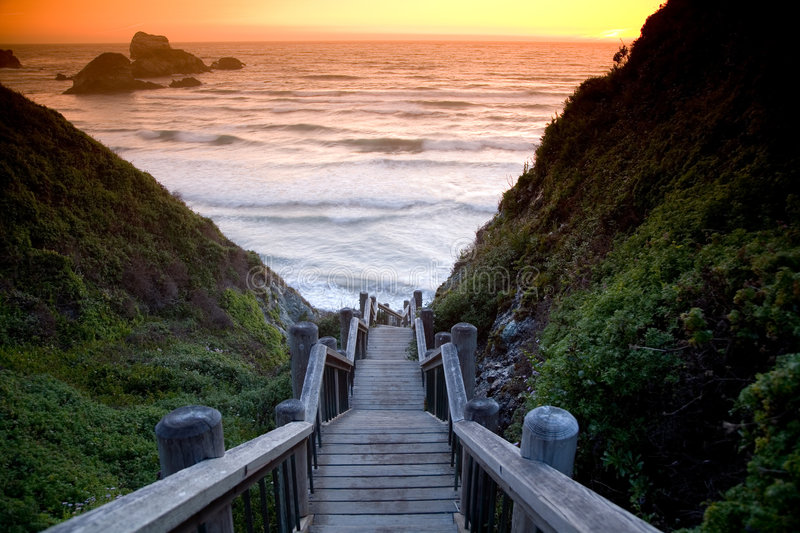 Beach stairs. Wooden stairs leading to the beach at sunset with rock formations in the background stock photo