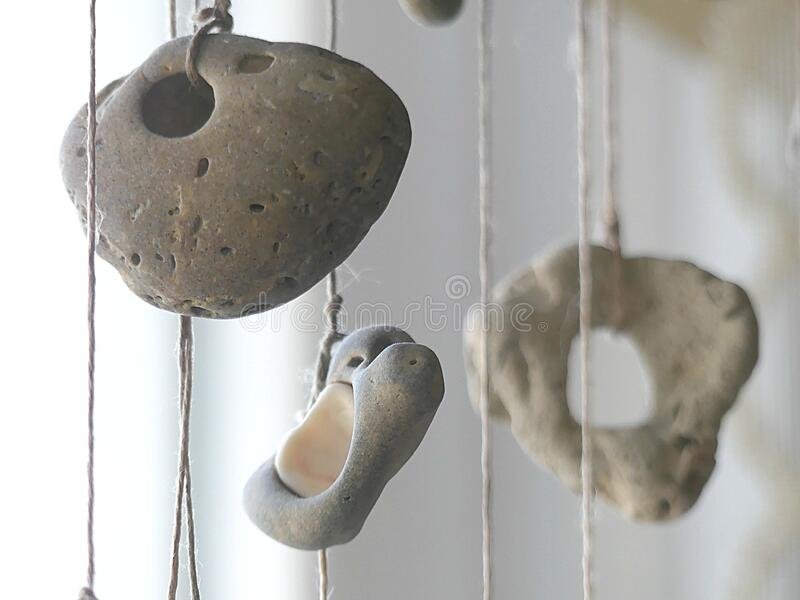 Beach stones with holes hanging on pieces of white twine in a window royalty free stock image