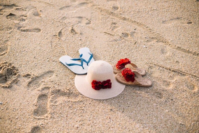 Beach  straw hat a couple of flip flops . Summer items on sandy beach. stock image