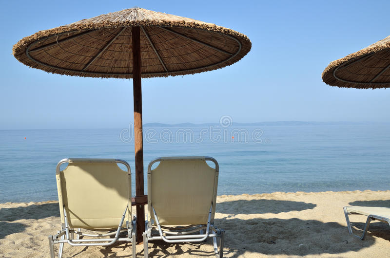 Beach straw parasols and pair of chairs royalty free stock images
