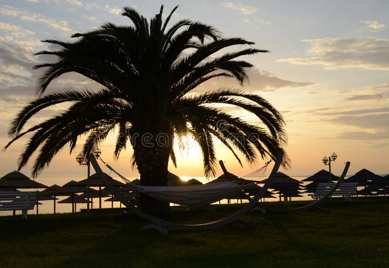 Beach straw umbrellas against the backdrop of a dawn sky on the shores of the Aegean Sea stock photo