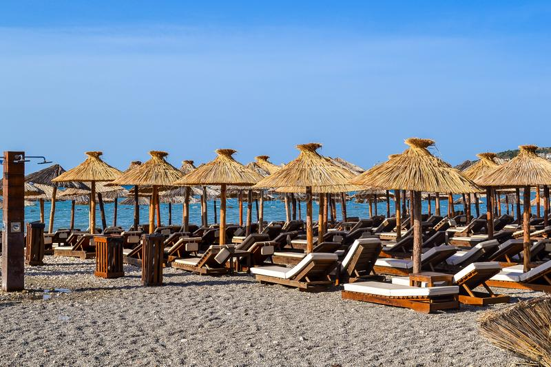 The beach with straw umbrellas from the sun and soft sun loungers. Adriatic coast. Summer. Without people. stock photo