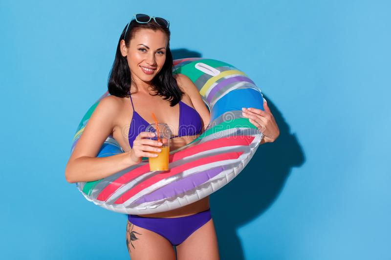 Beach style. Woman in bikini wearing swim ring and sunglasses up the head standing isolated on blue wall with smoothie royalty free stock photos