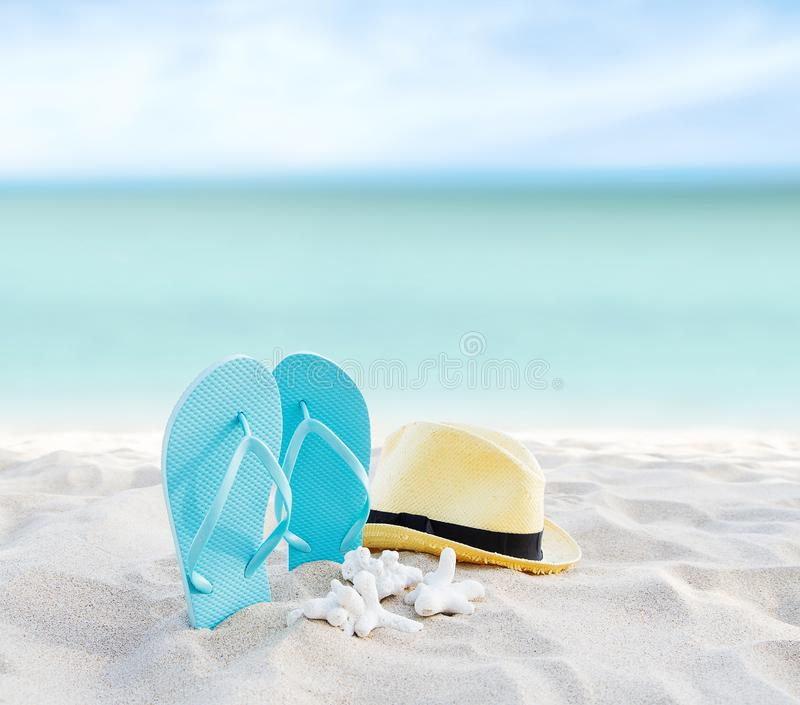 Beach summer holiday background. Flip flops and hat on sand near ocean. Summertime accessories on seaside. Tropical vacation royalty free stock photo