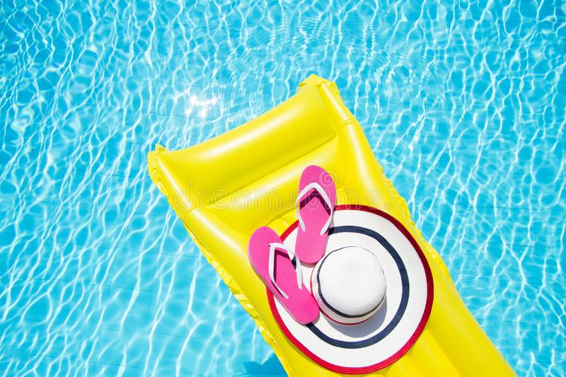 Beach summer holiday background. Inflatable air mattress, flip flops and hat on swimming pool. Yellow lilo and summertime royalty free stock image