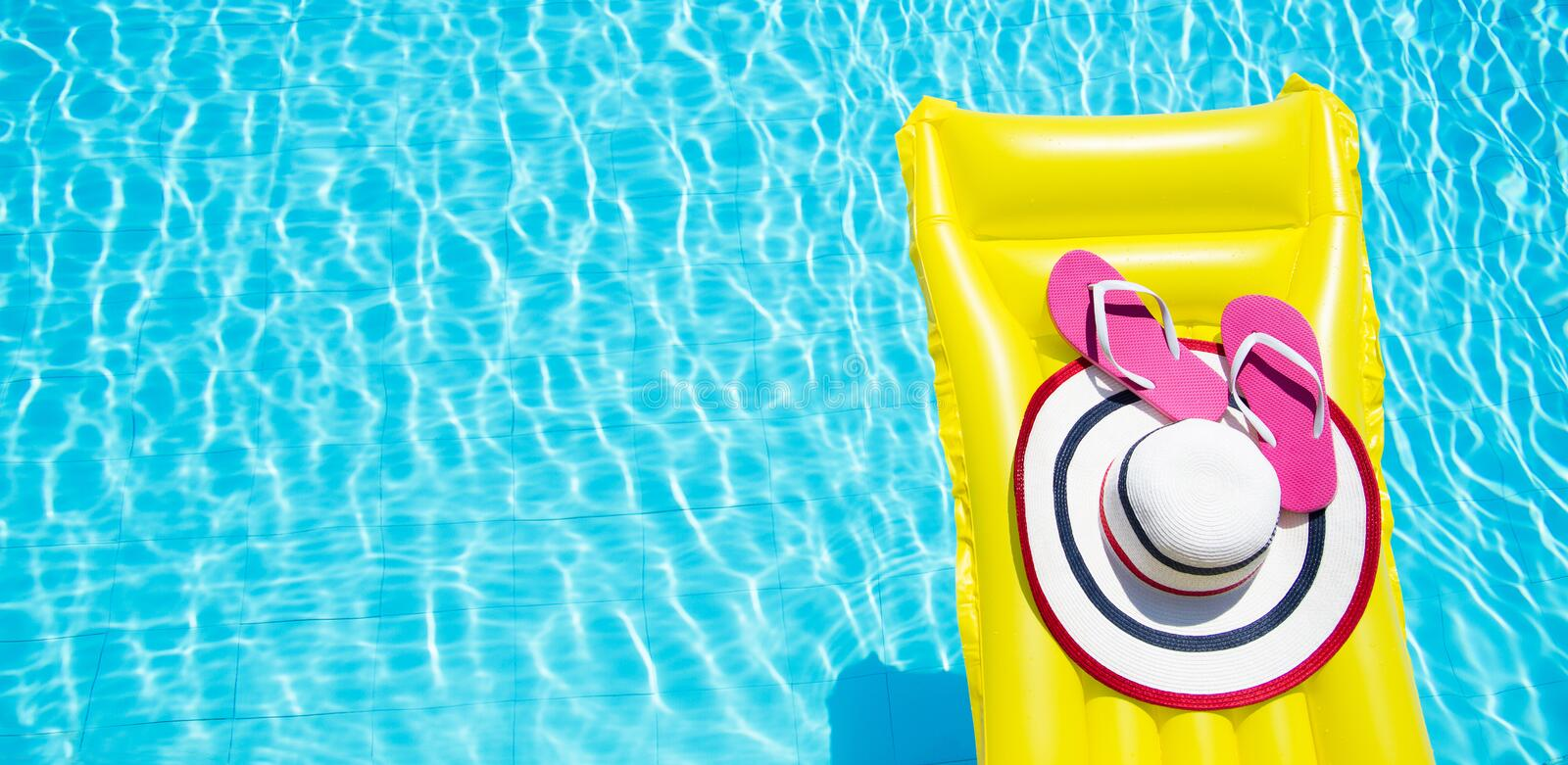 Beach summer holiday background. Inflatable air mattress, flip flops and hat on swimming pool. Yellow lilo and summertime stock photo