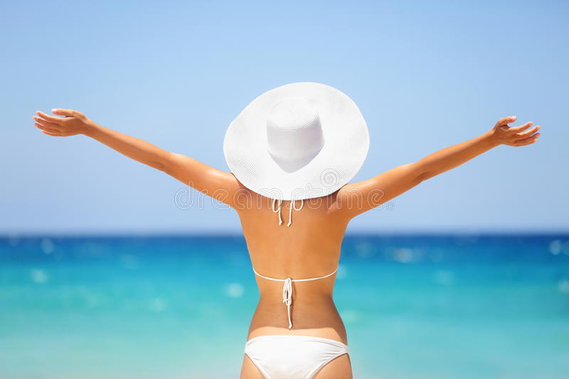 Beach summer holidays happy freedom woman. Beach summer holidays woman in happy freedom concept with arms raised out in happiness. Woman model wearing white royalty free stock photo