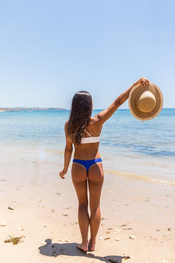 Beach summer holidays woman in happy freedom concept with arms raised out in happiness. Latin Woman wearing white bikini with. Beach summer holidays woman in stock photography