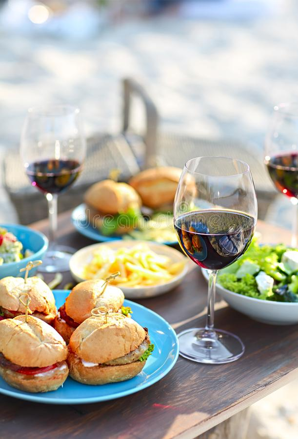 Picnic table with red wine glasses. Beach summer picnic table with red wine glasses royalty free stock photos
