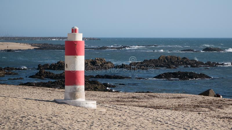 Beach in the summer in Portugal with small red and white lighthouse. A small red and white lighthouse overlooks a beach in the summer in Portugal with rocks and stock photography